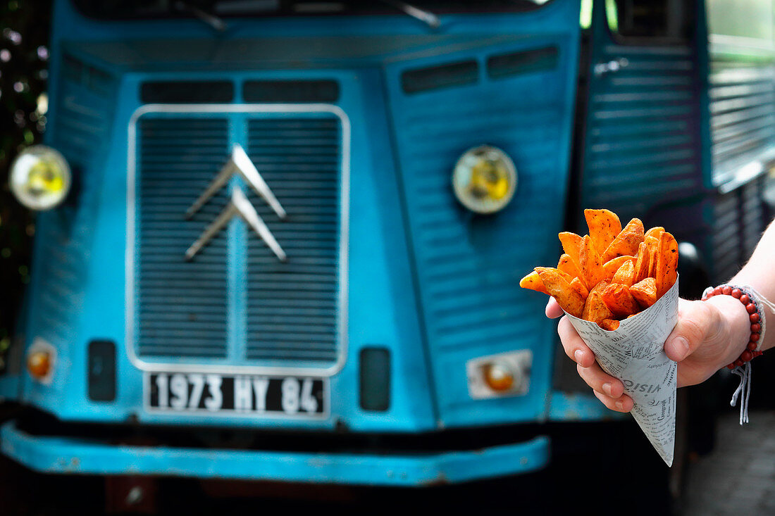A hand holding a cone of sweet potatoes and chips in front of a food truck