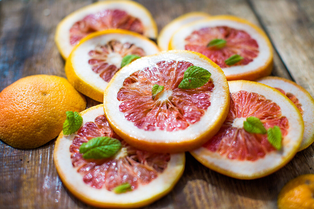 Pink grapefruit slices with mint leaves on a wooden background