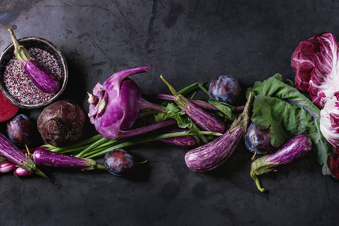 An arrangement of purple vegetables and fruit on a white surface (seen from above)