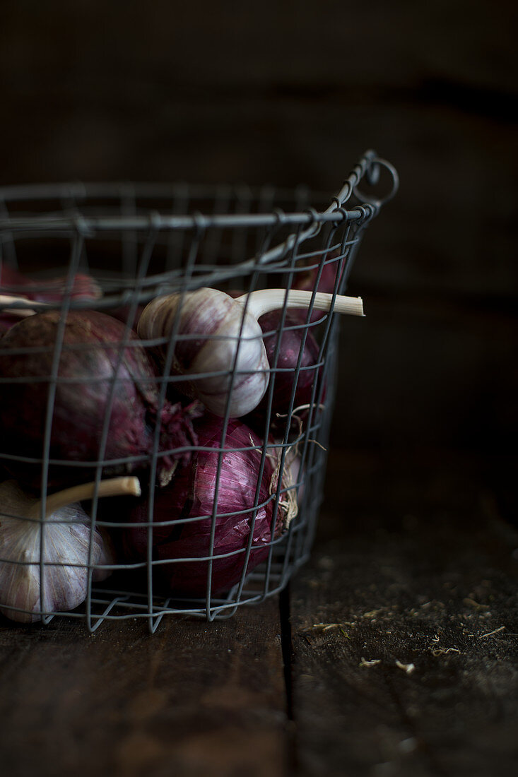 Garlic and red onions in a wire basket