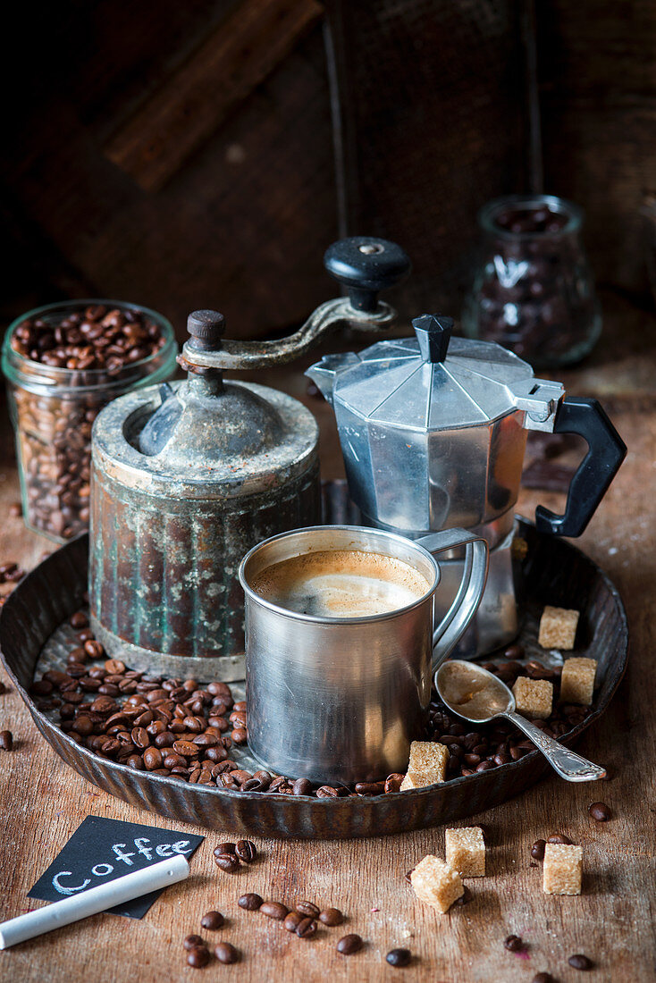 An arrangement of coffee with an espresso jug, a coffee mill, sugar and coffee beans
