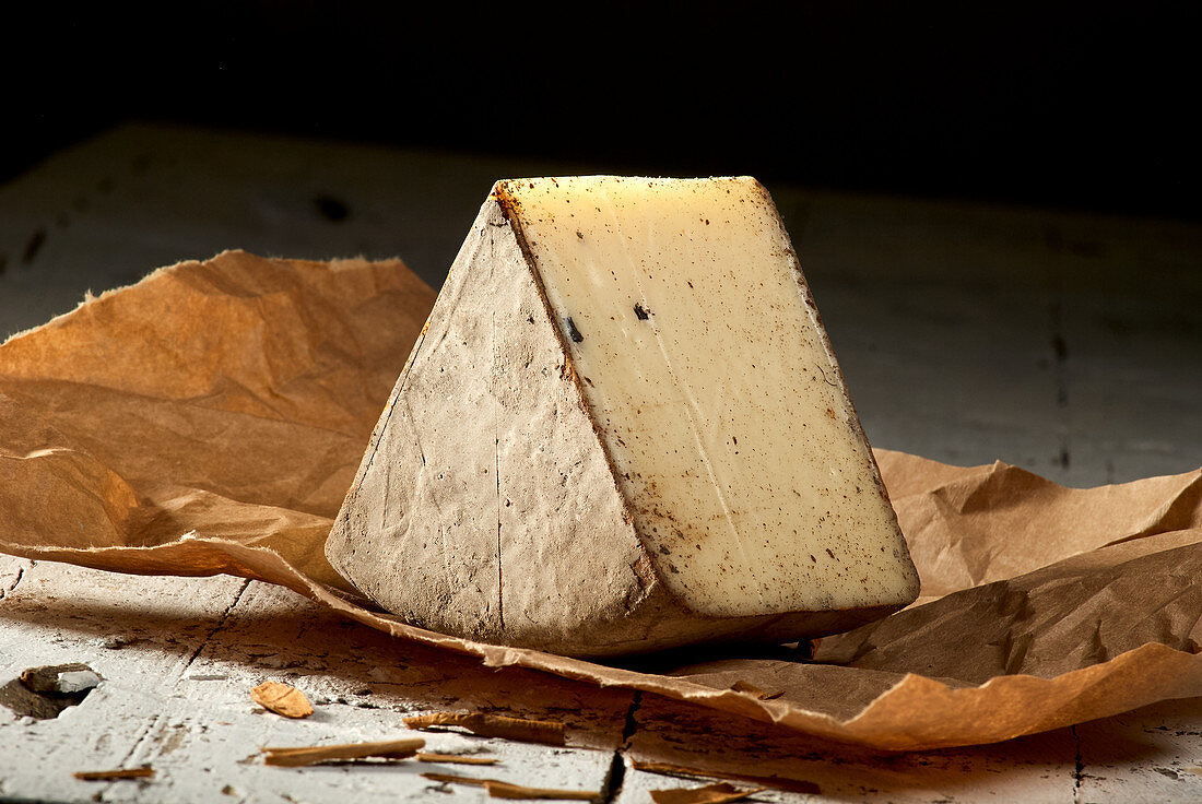 A wedge of pecorino with potash and cinnamon on paper