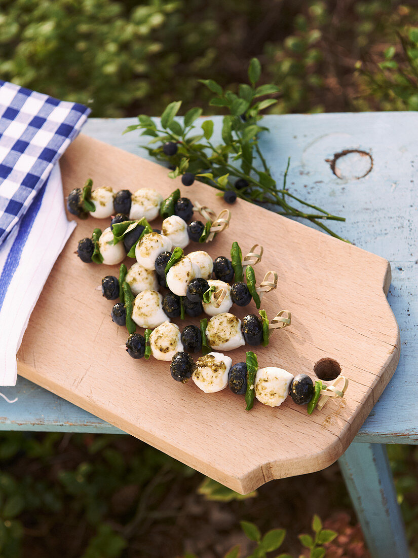 Mozzarella skewers with basil and blueberries