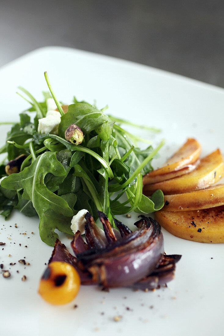 Arugula salad with grilled peach, grilled red onion, feta and pistachios
