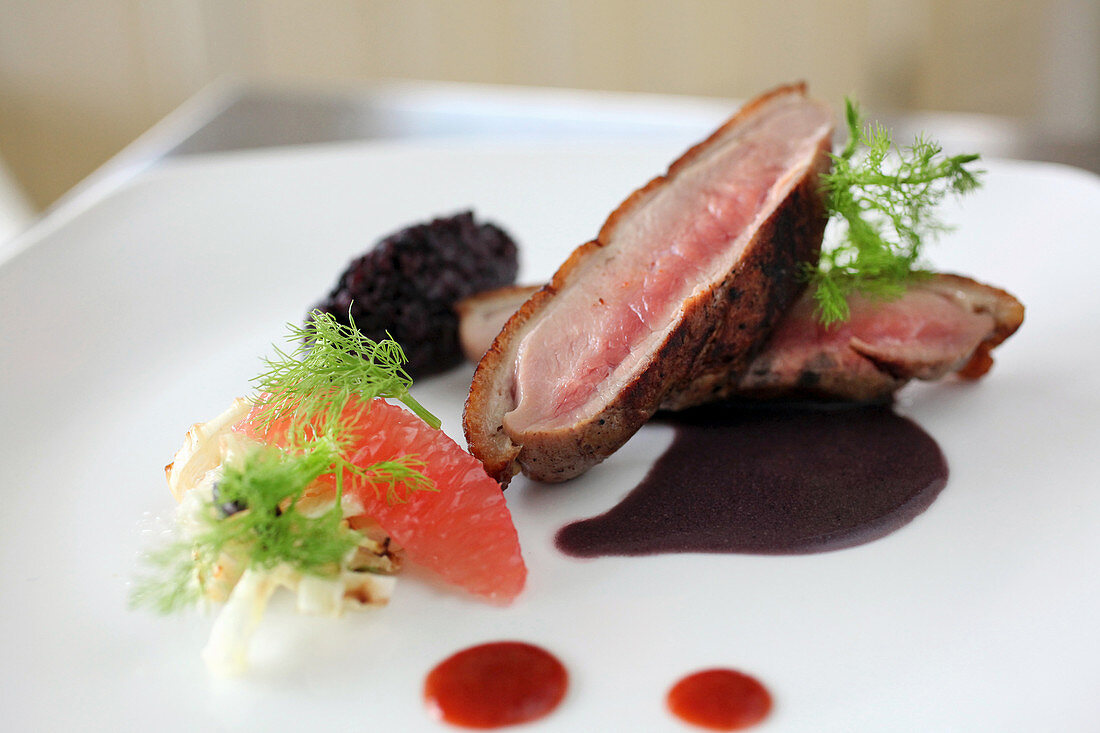 Roasted duck breast with black rice, grapefruit and fennel