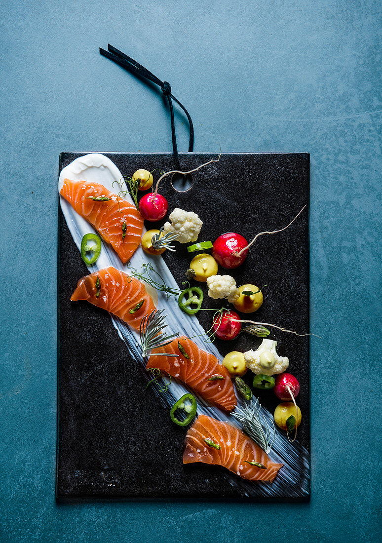 Salmon platter with radishes, cauliflower and chilli peppers