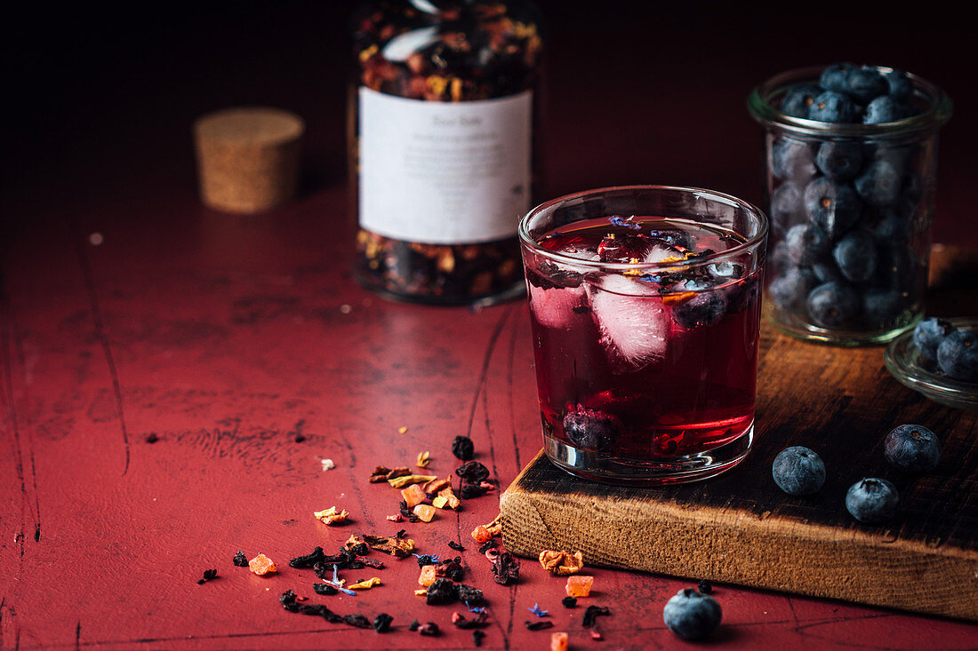 A cocktail with berries and tea