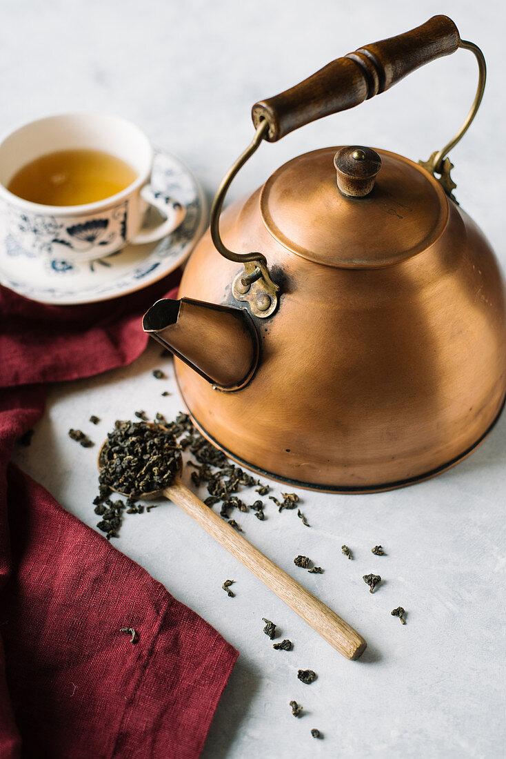 Green tea in a copper pot and a tea cup