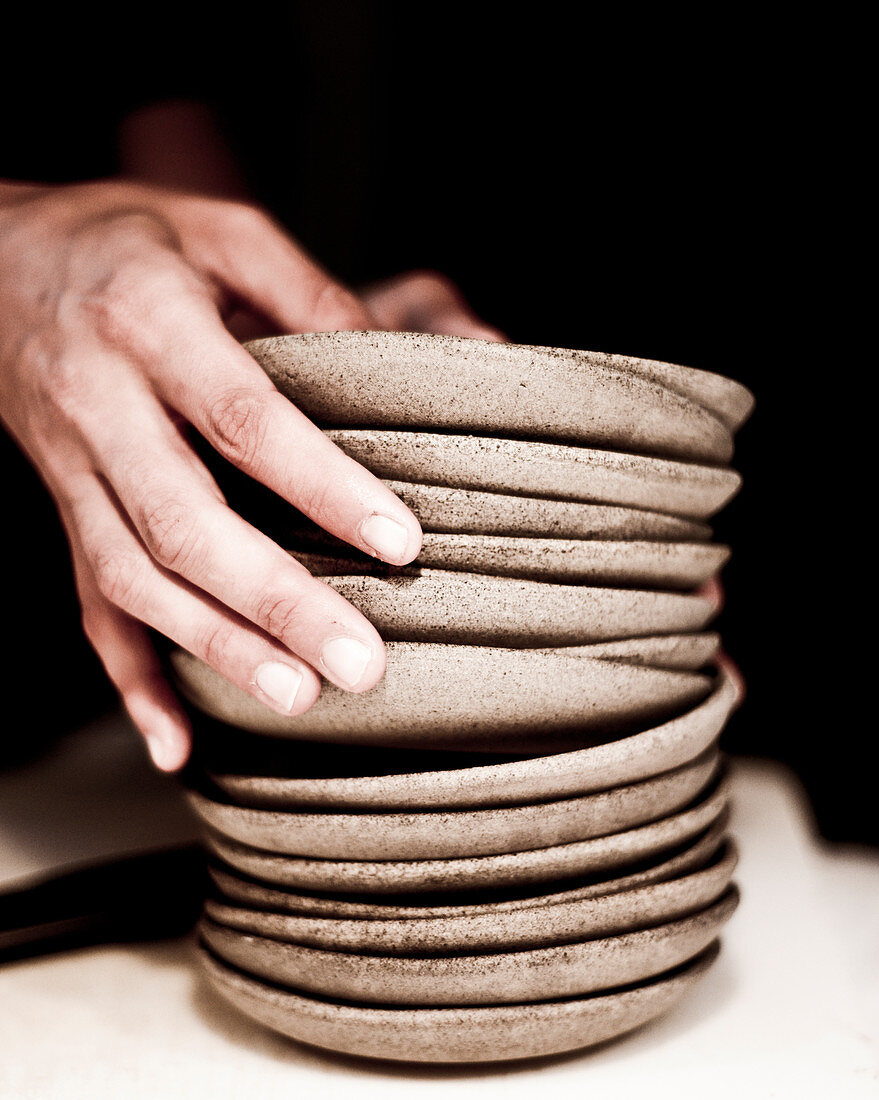 Hands stacking ceramic plates