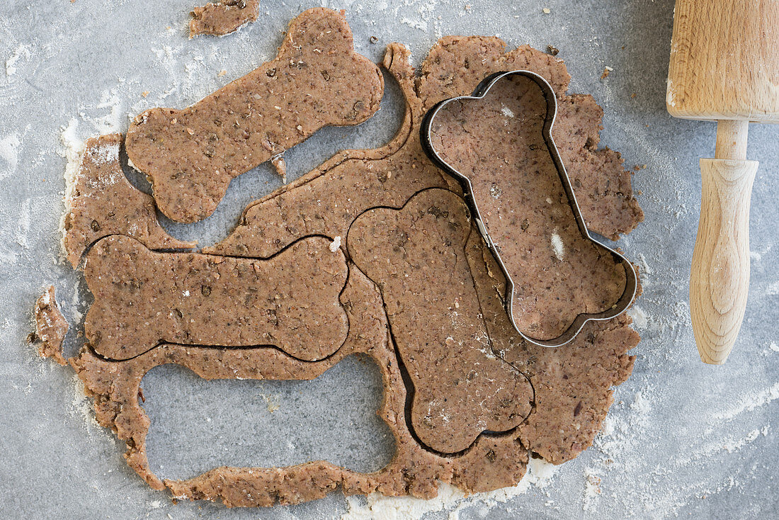 Dough and a bone-shaped cookie cutter for dog biscuits