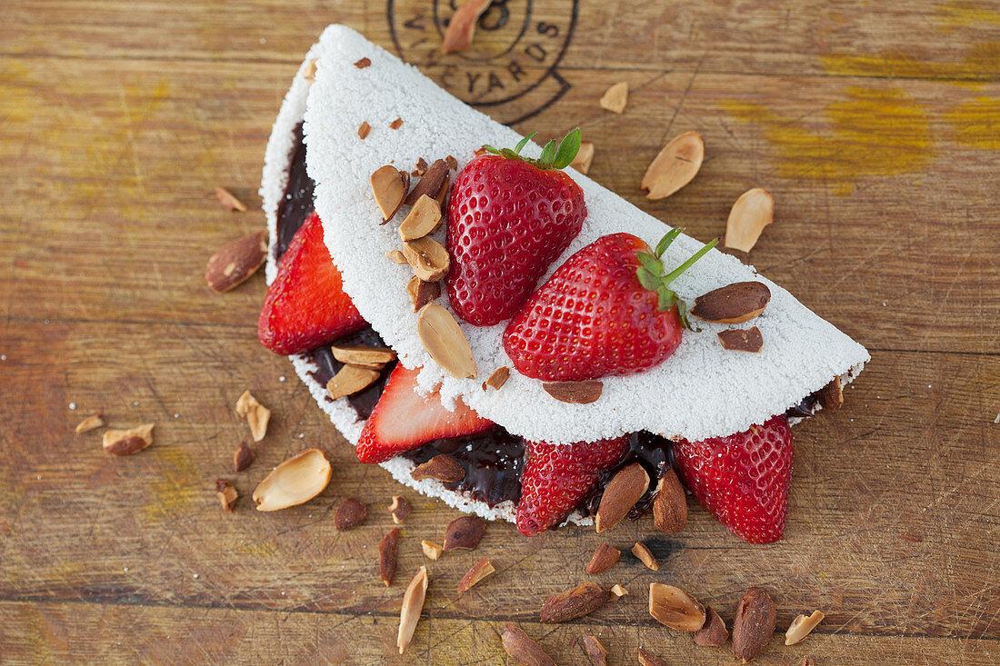 Tapioca filled with brigadeiro (chocolate truffle pralines), strawberries and almonds (Brazil)