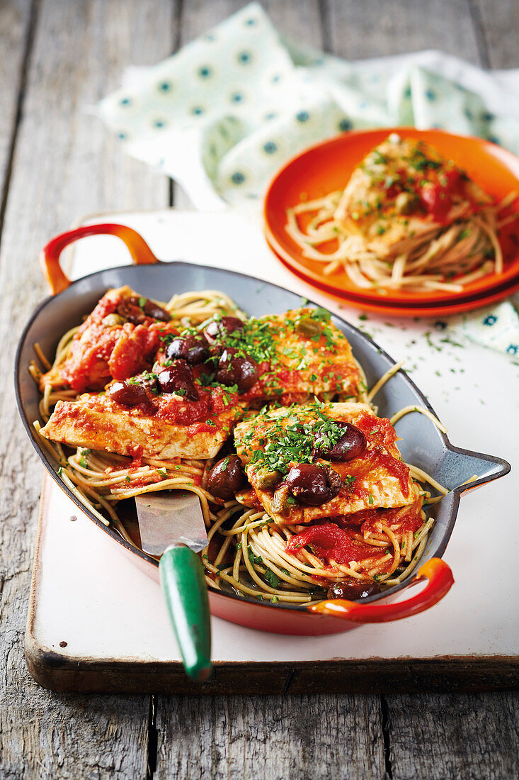 Spaghetti Puttanesca with fish fillets and olives