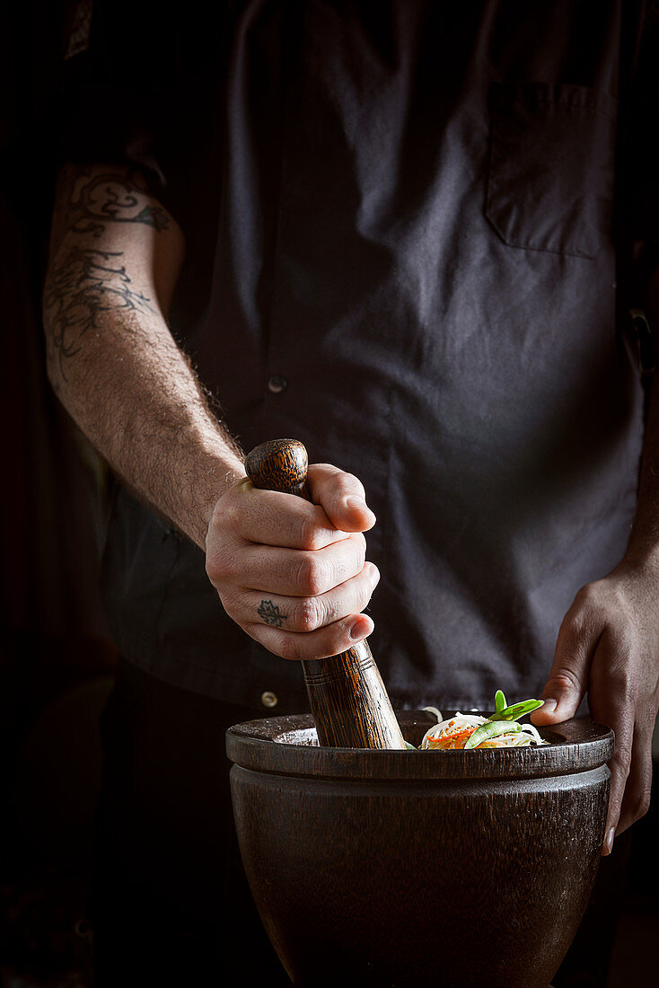A chef preparing an Asian salad in a mortar