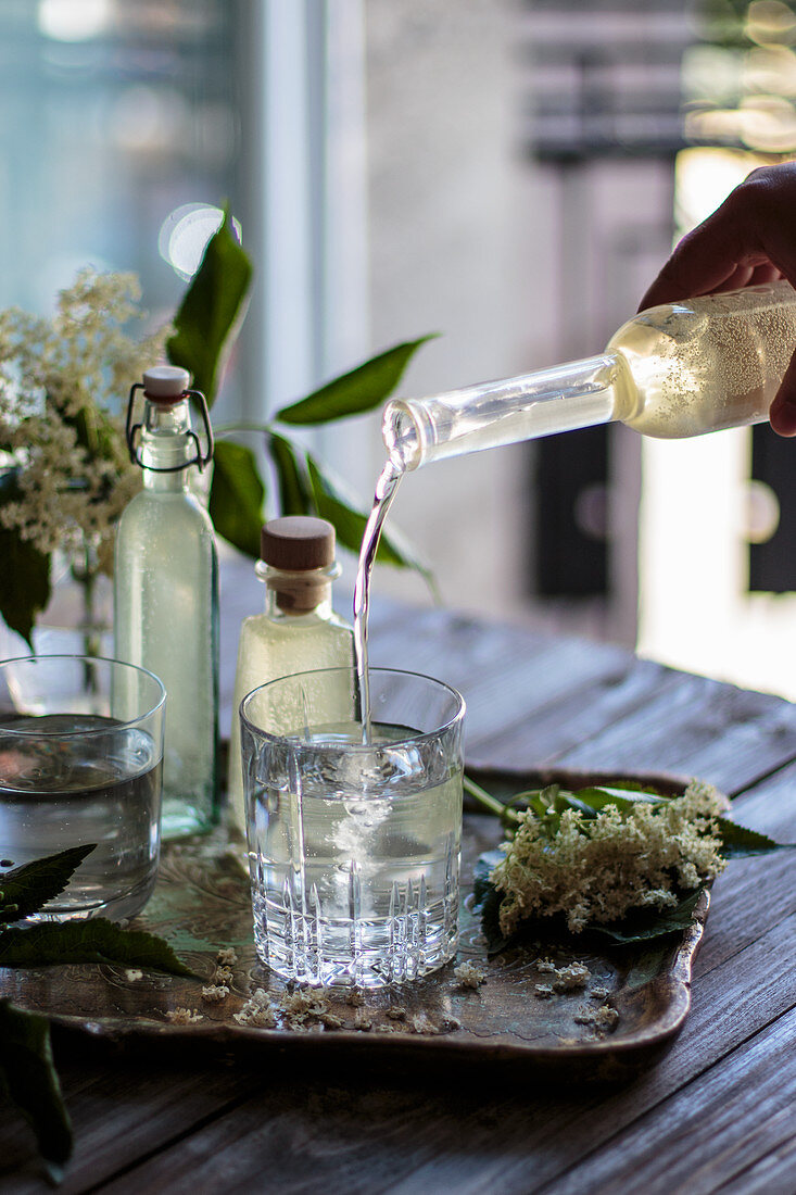 Pouring elderflower syrup into glass