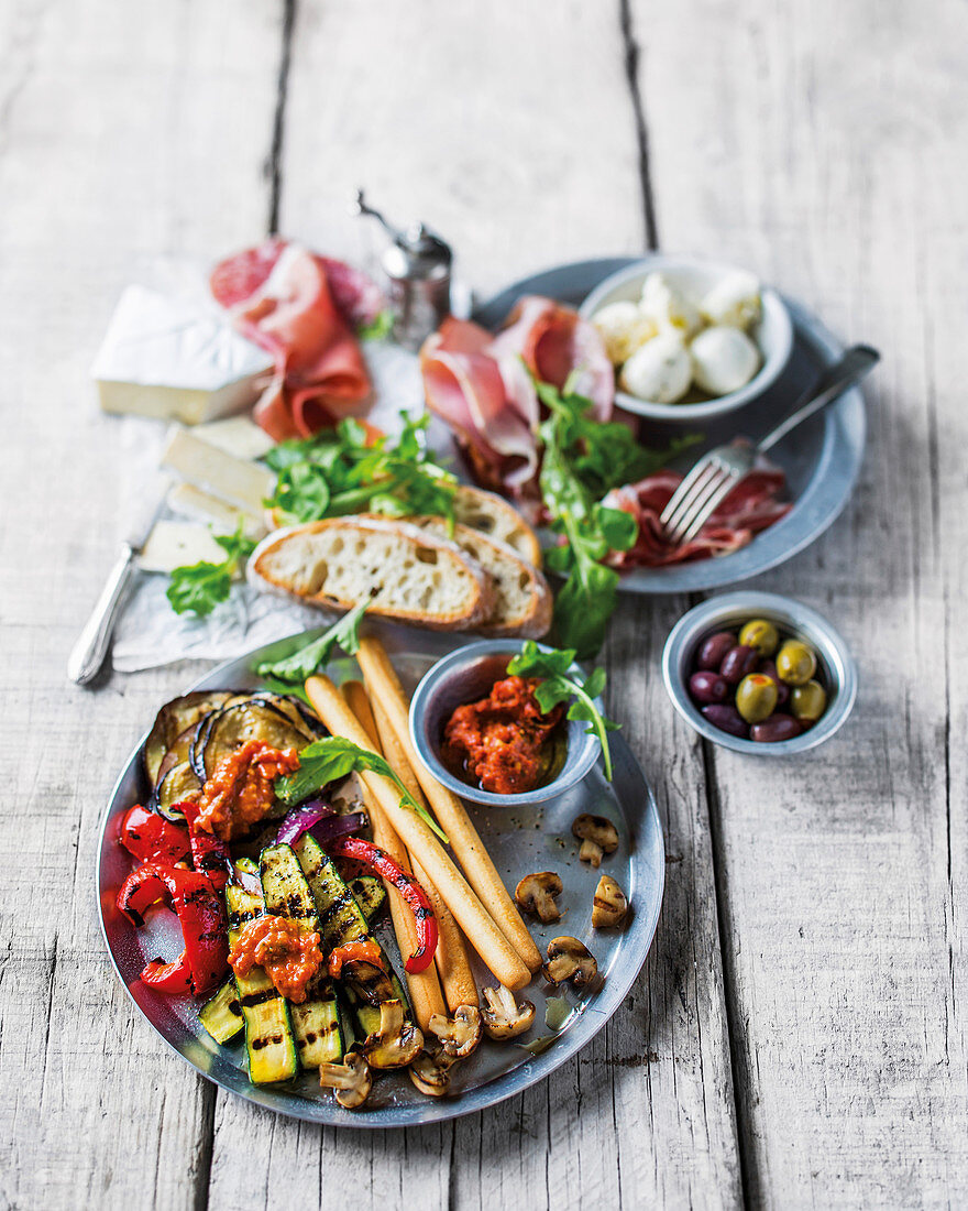 An appetizer tableau with grilled vegetables and bread sticks
