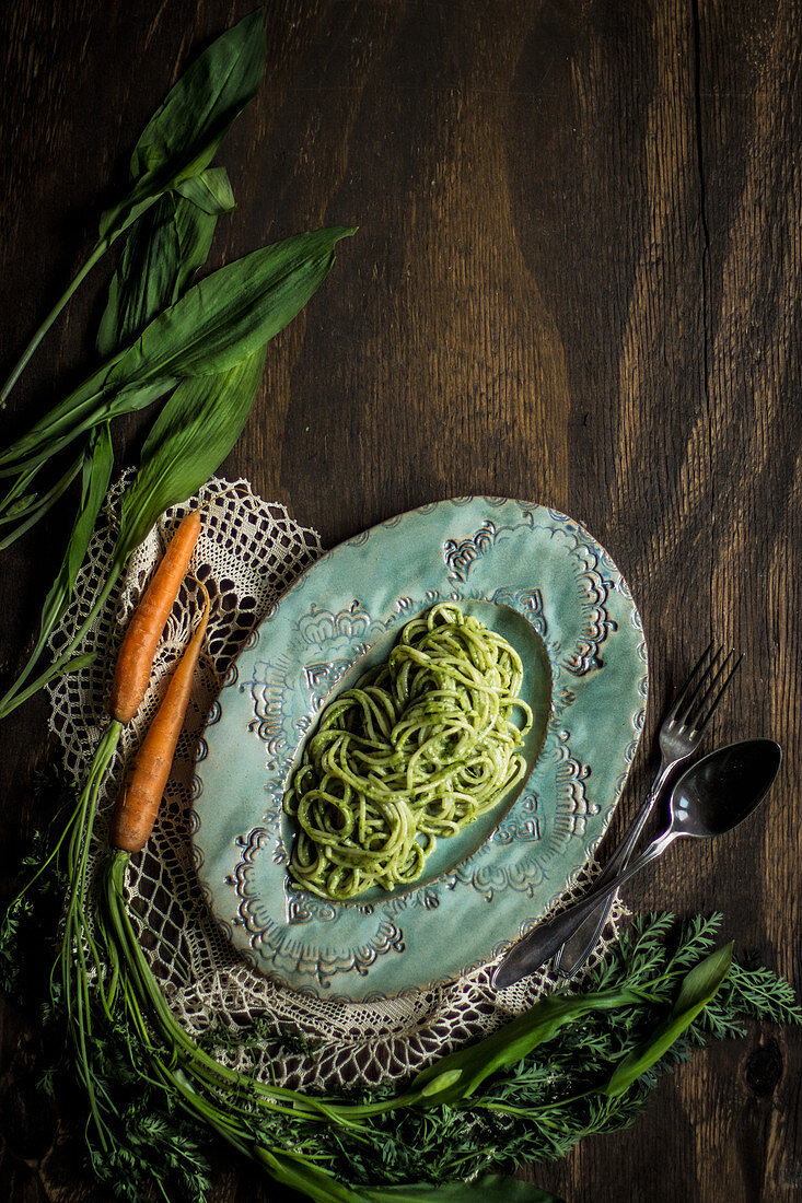 Pasta with carrot and wild garlic pesto on a blue plate