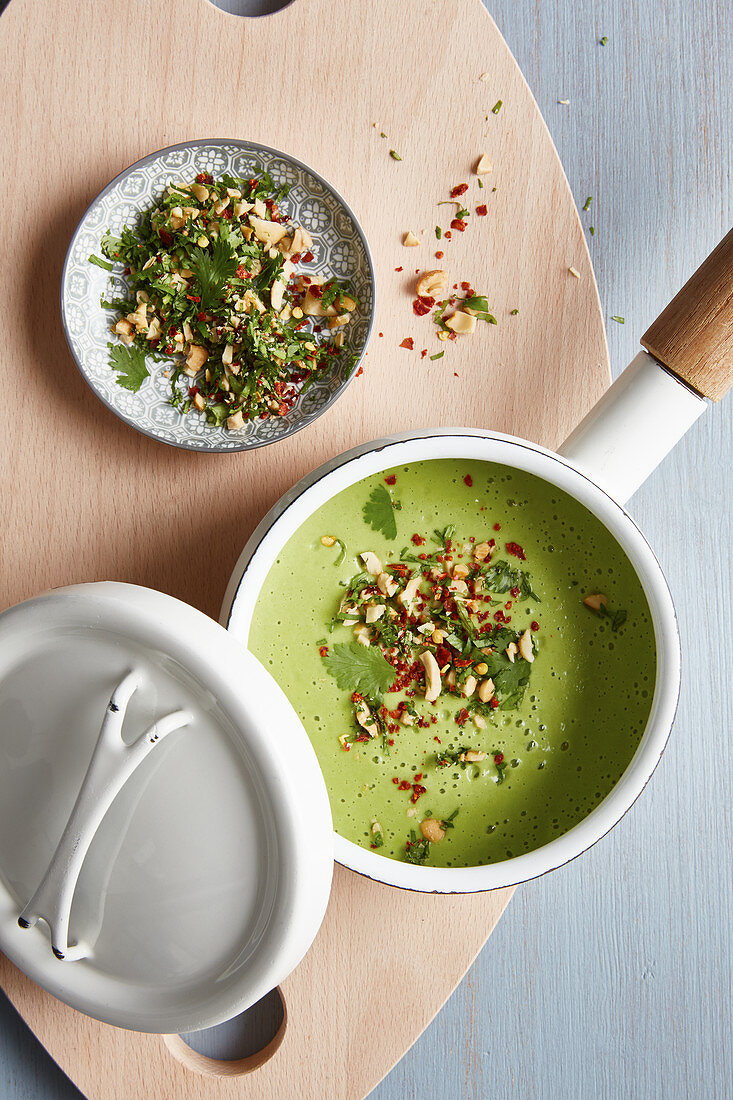 Vegan broccoli and coconut soup with cashew nuts and chilli flakes