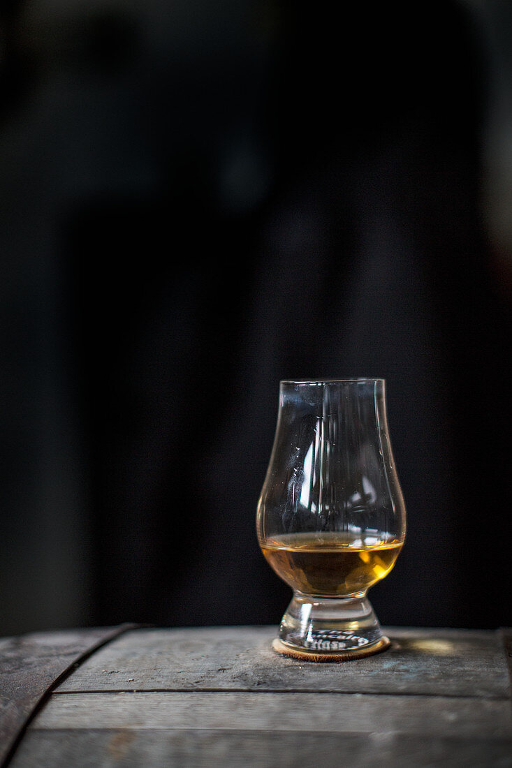 A glass of whisky on a wooden barrel