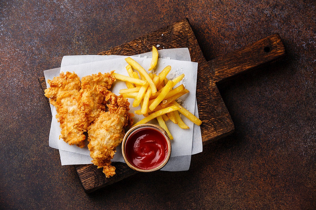 Fish and Chips, british fast food with ketchup sauce on dark background