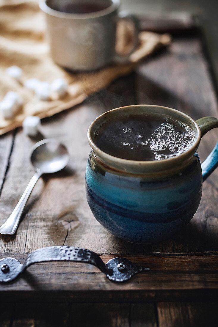 Handmade stone mug of steaming hot tea on rustic wood serving tray