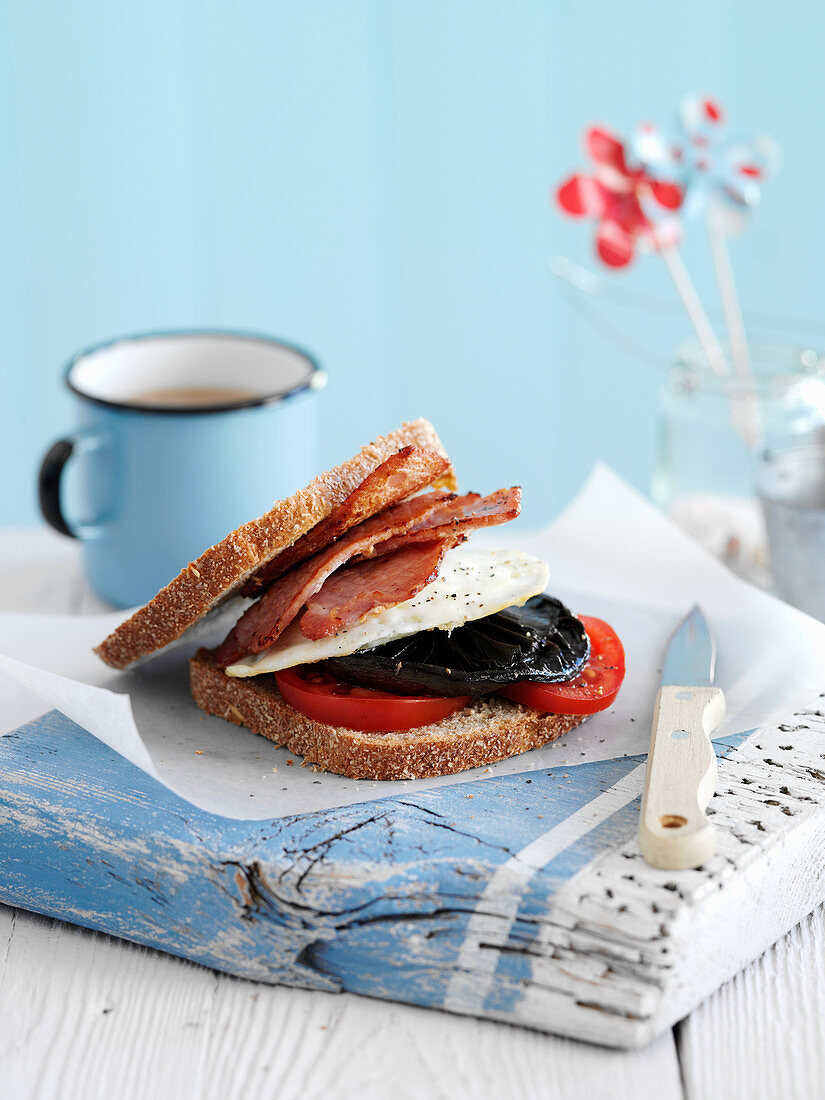 A sandwich with bacon, egg, mushroom and tomatoes