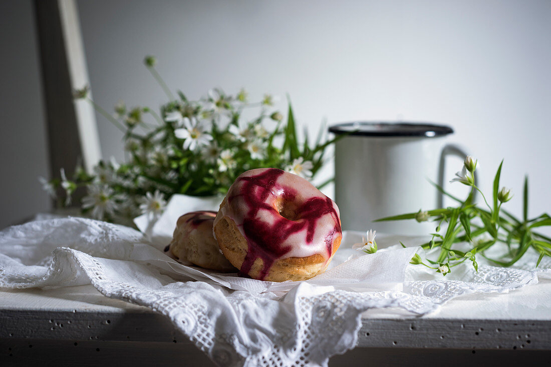 Vegan doughnuts with two types of glaze on an old wooden chair with coffee and flowers
