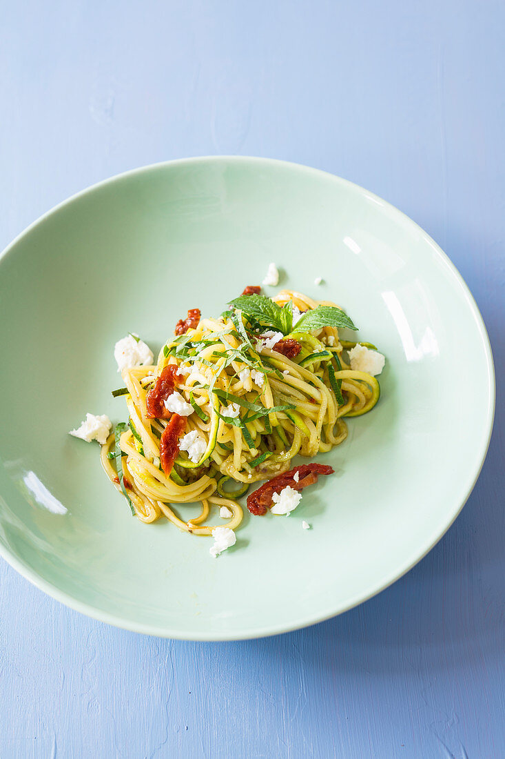 Courgette noodles with dried tomatoes, feta cheese and mint