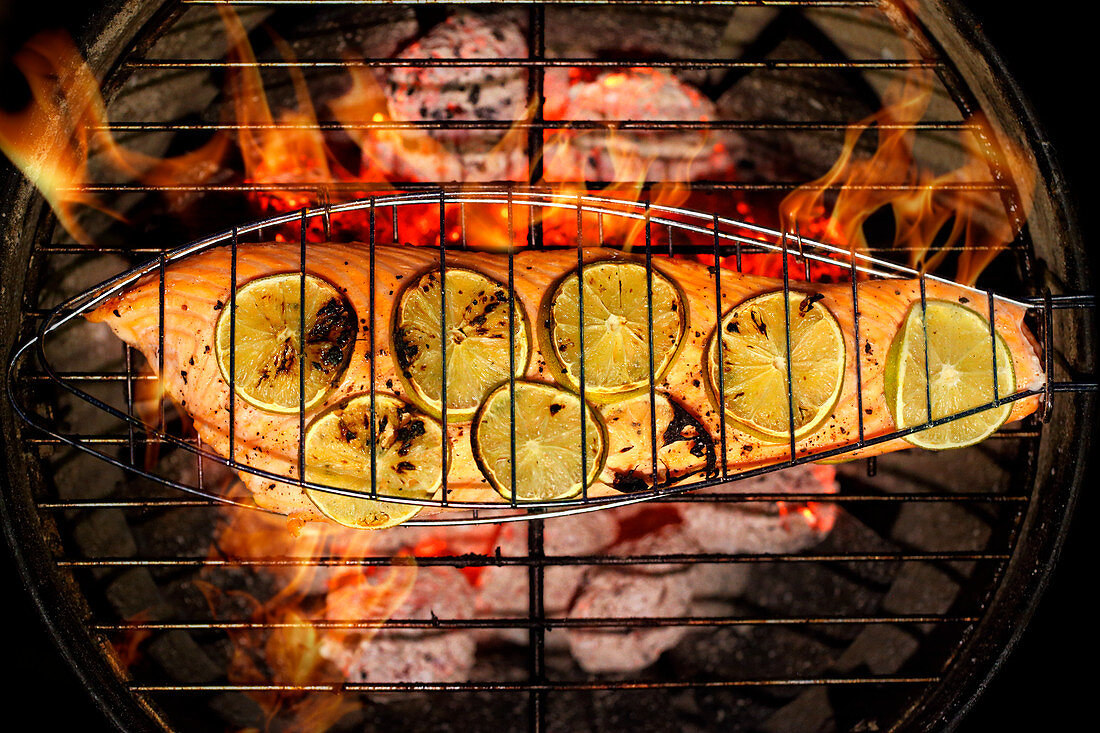 Salmon fillet with lime slices in a fish grilling basket over a charcoal grill