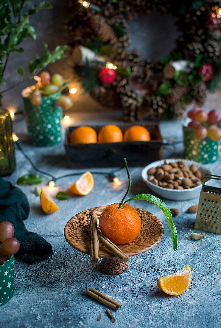 Mandarins, almonds, grapes, cinnamon sticks, fairy lights and a Christmas wreath