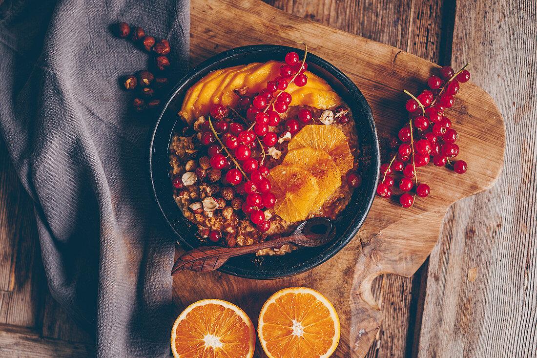 Autumnal porridge with cinnamon, hazelnuts, orange slices, redcurrants and mango