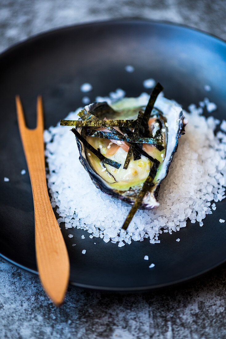 An oyster with algae strips on a bed of salt