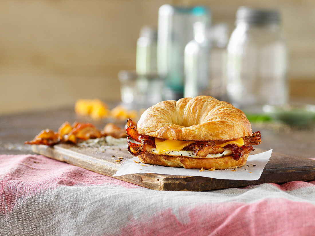 A croissant sandwich with egg, bacon and cheese