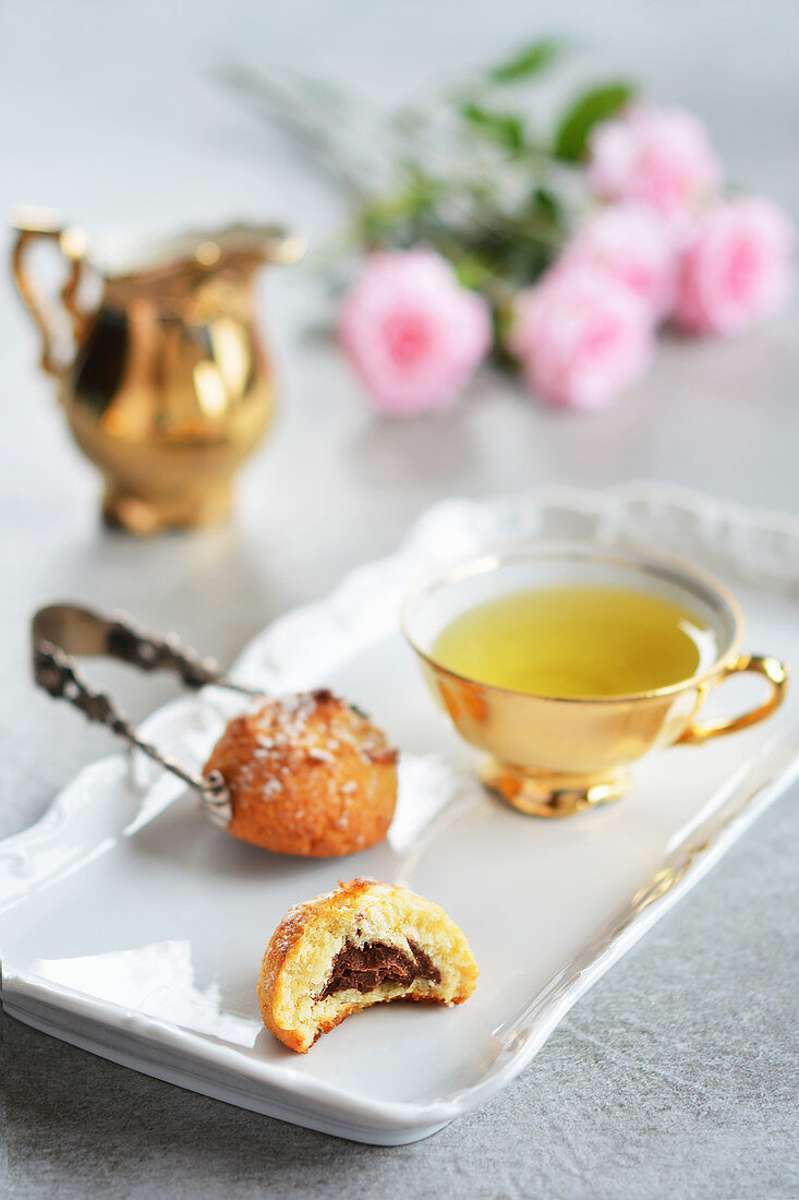 Almond cakes with chocolate filling and tea on a porcelain tray
