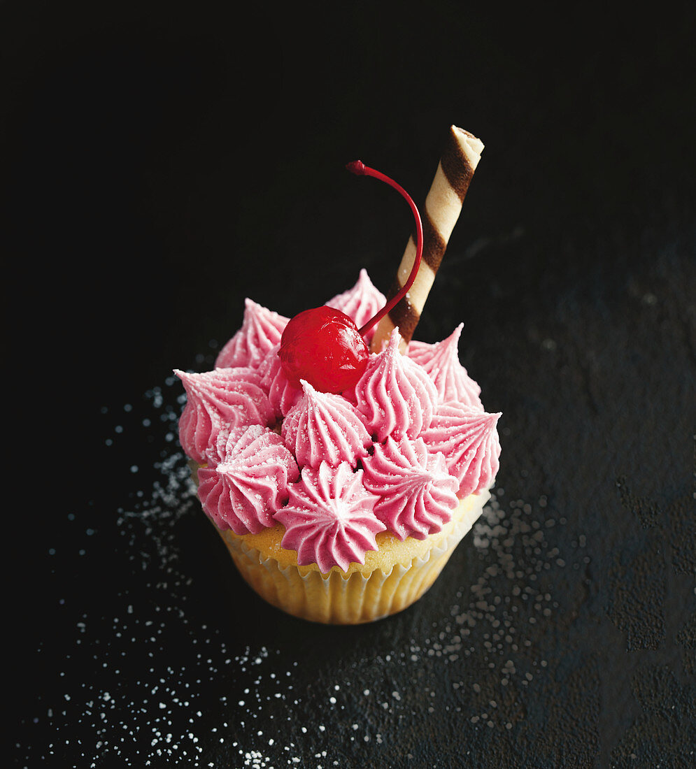 A Shirley Temple cupcake decorated with a cocktail cherry