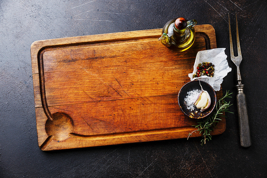 Wooden cutting board background with seasoning, herbs and kitchen fork