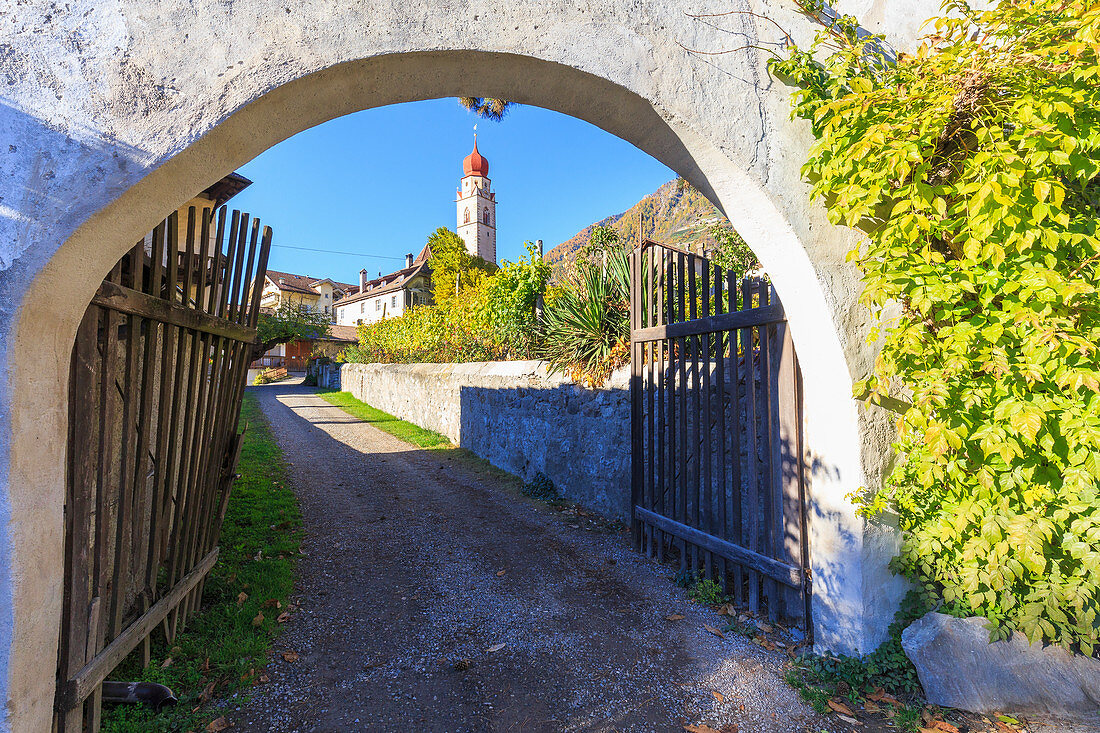 A view through an archway of the village of Partschins and the church, Vinschgau, South Tyrol, Italy