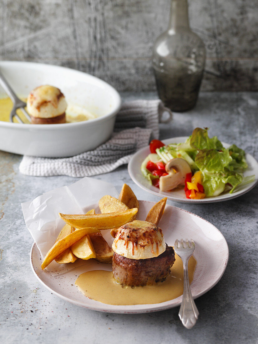Pork fillet with apple halves, curry sauce, chips and a summer salad