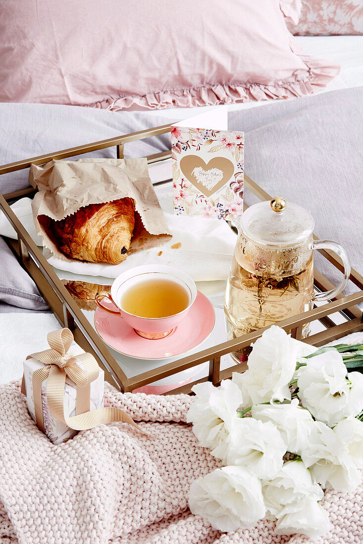 Breakfast tray with tea, croissant and greeting card on bed, flowers and small gift