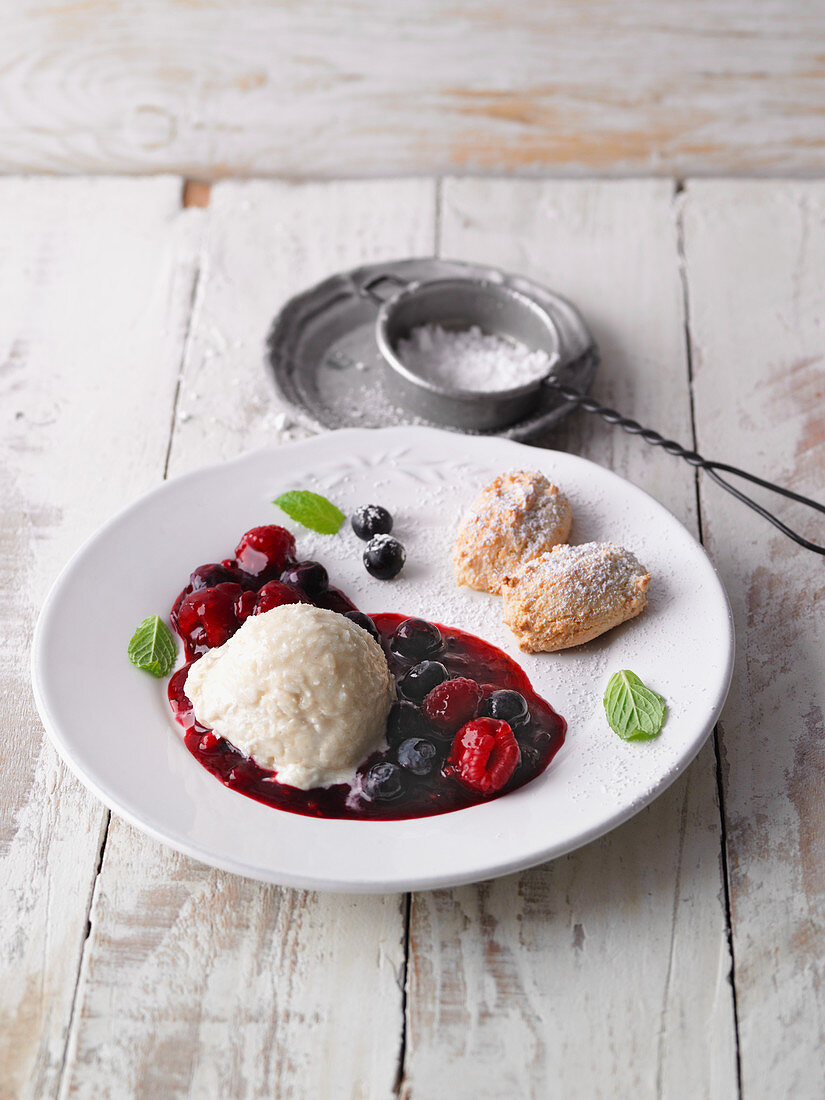 Vanilla and coconut mousse with berry compote and almond biscuits