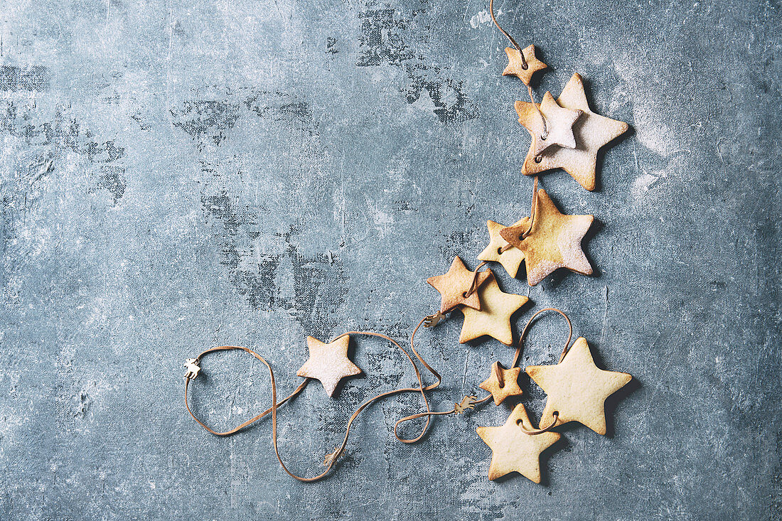 Homemade shortbread star shape sugar cookies different size with sugar powder on thread over blue texture surface