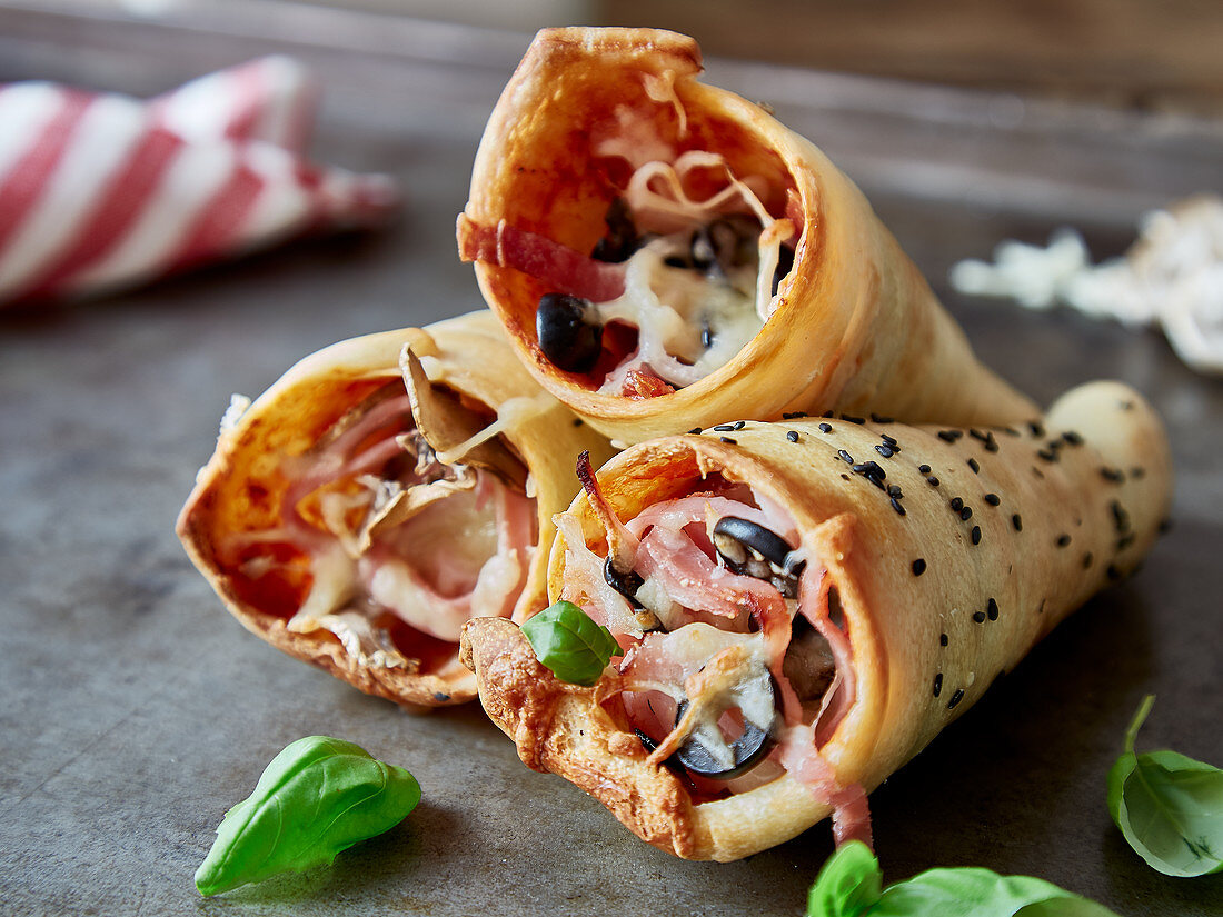 Pizza horns with ham, mozzarella, mushrooms, and olives