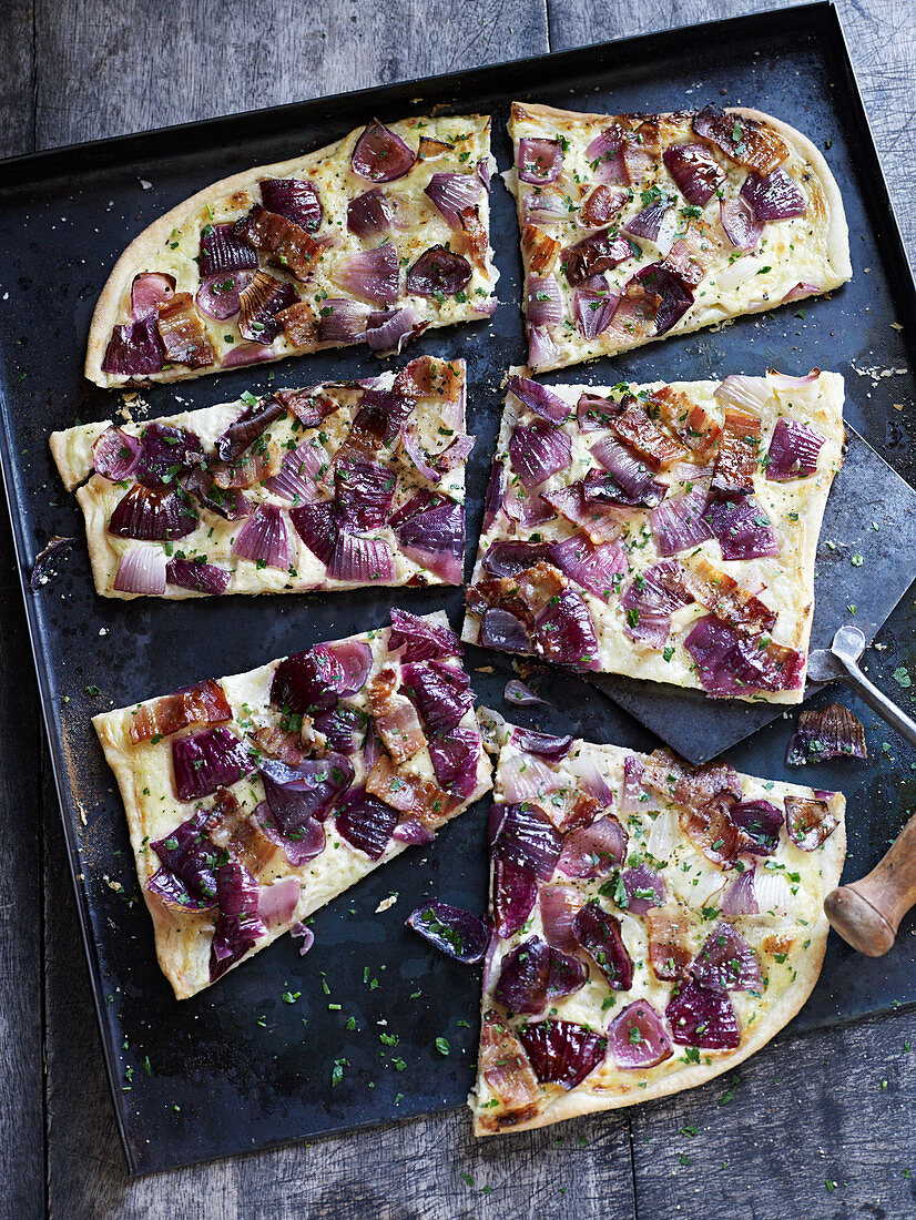 Tarte flambée with red onions on a baking tray