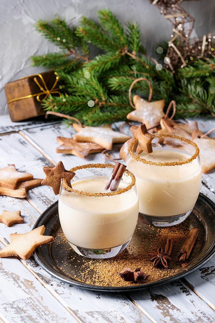 Eggnog Christmas milk cocktail with cinnamon, served in two glasses