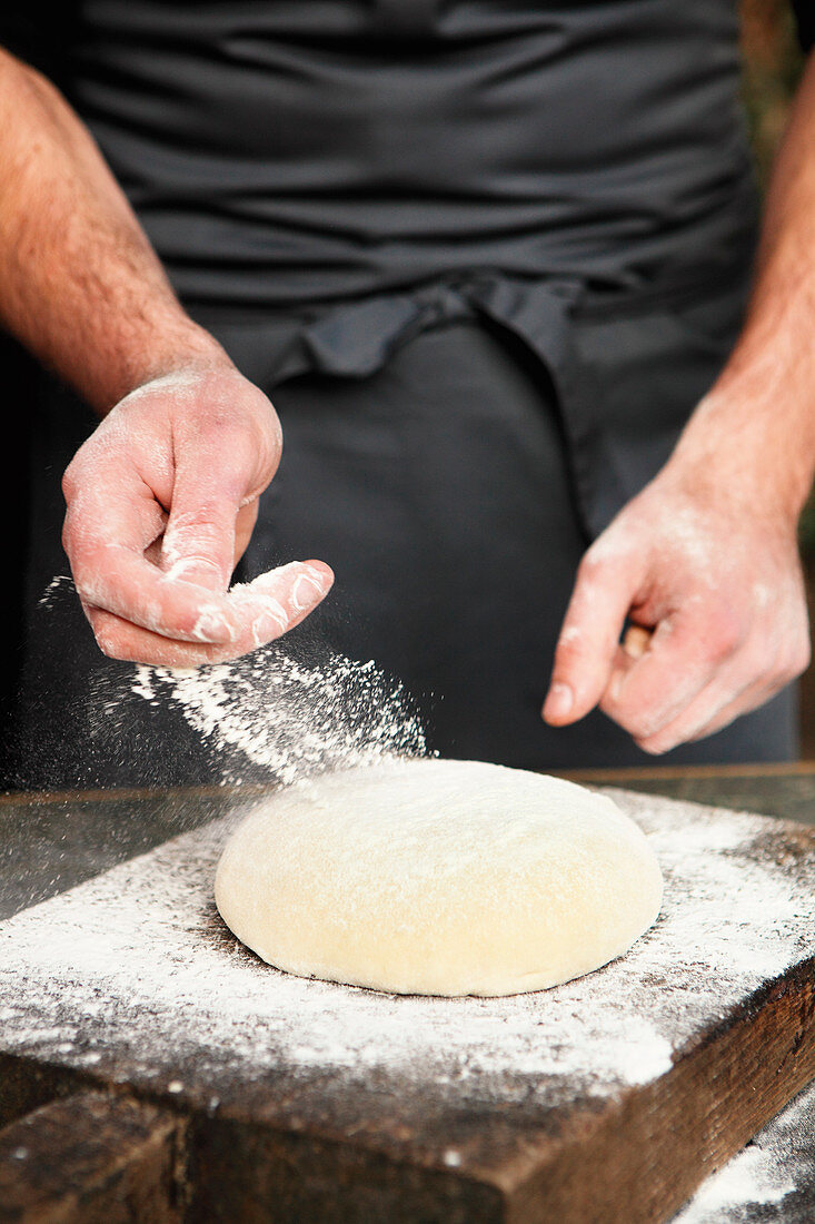 Yeast dough being dusted with flour