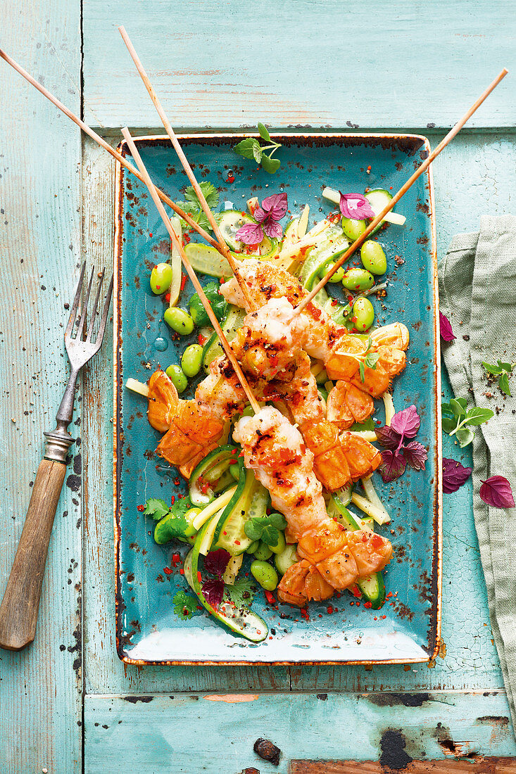 Grilled marinated scampi skewers with a sweet and sour cucumber salad