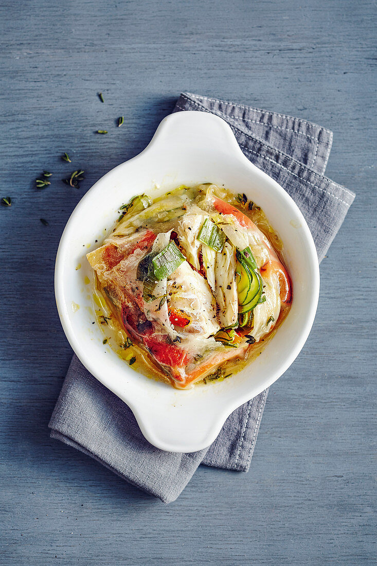 Oven-baked cod fillet with vegetables in rice paper sacks
