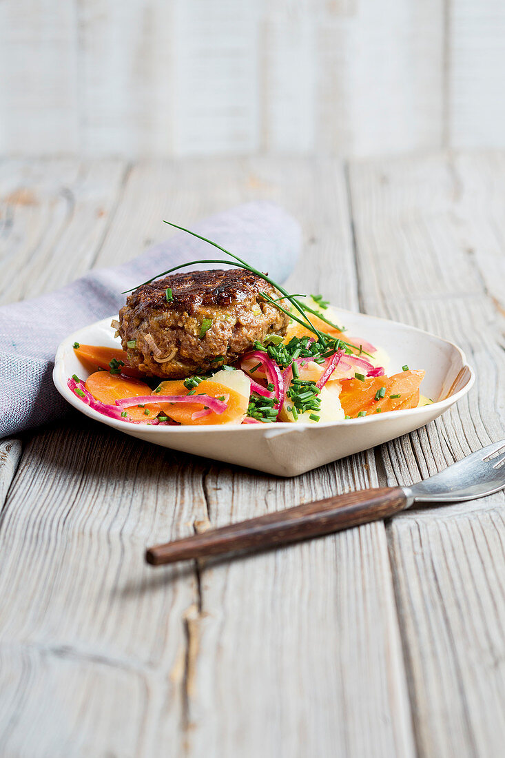 A meat patty with a parsnip and potato salad
