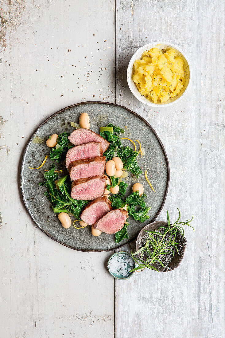 Roasted saddle of lamb with kale and white beans
