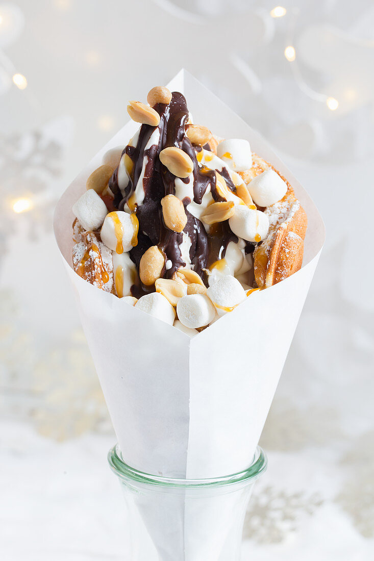 A bubble waffle with frozen yoghurt, chocolate sauce, peanuts, caramel sauce and marshmallows (Christmas)