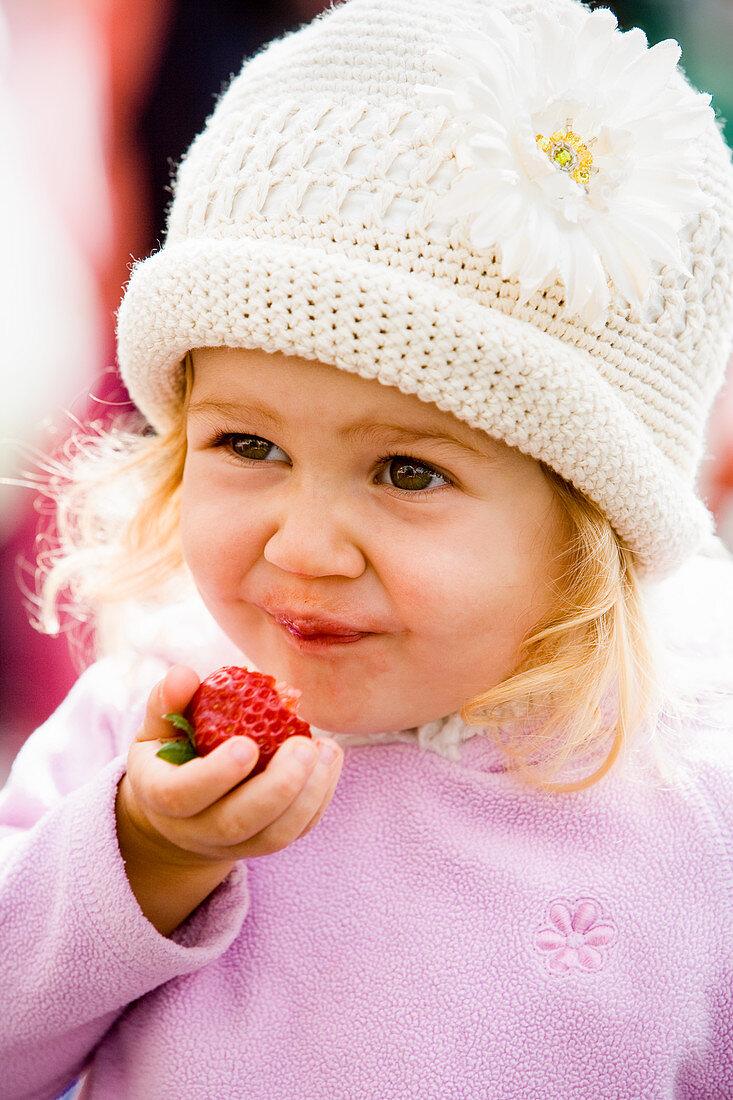 Little girl enjoying fresh strawberries at the famers market